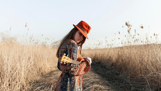Side view of bohemian woman posing with ukulele in nature