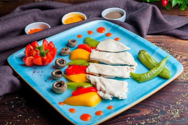 木製のテーブルで野菜と鶏の胸肉をゆでた側面図