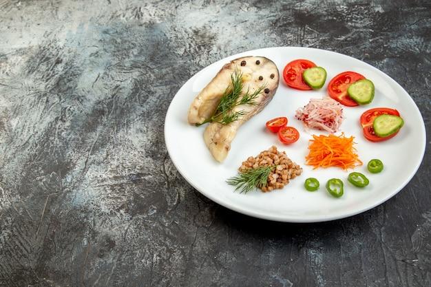 Vista laterale del grano saraceno di pesce bollito servito con verdure verdi su un piatto bianco sulla superficie del ghiaccio