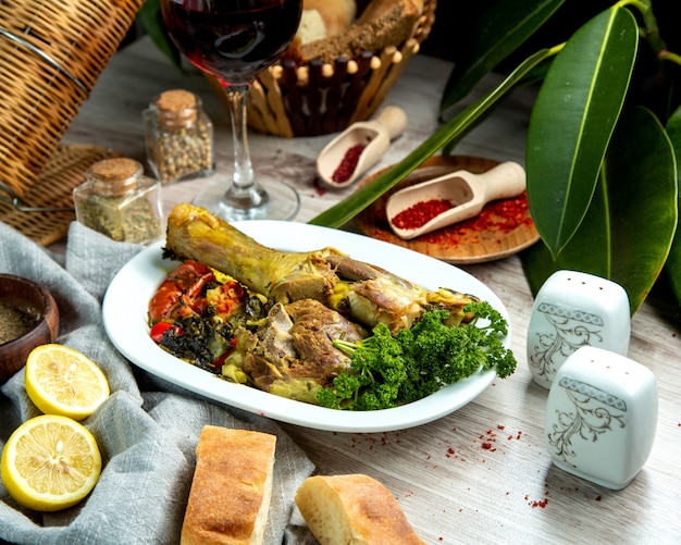 Side view boiled lamb leg with vegetables with spices lemon slices and bread