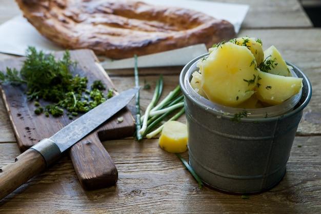 側面図ゆでたジャガイモとネギとパンと木製のテーブルのテーブルにナイフ