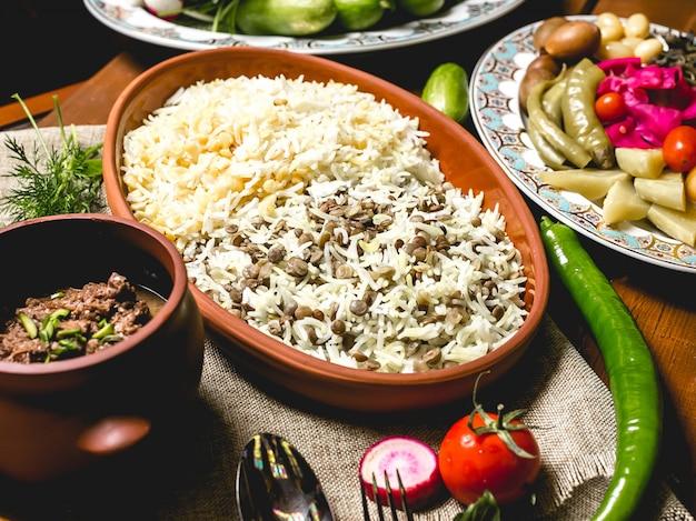 Вид сбоку отварной рис на тарелку с мясом в горшочке и солеными овощами