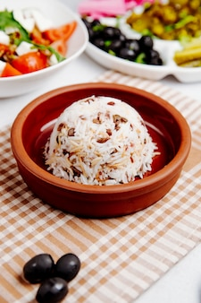 Side view of boiled rice with beans in a wooden bowl