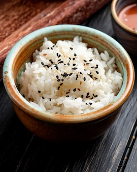 Side view of boiled rice with black seeds in a clay bowl on wood