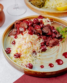 Side view of boiled rice with meat and cherries