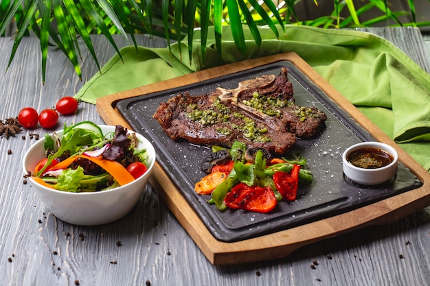 Side view bone steak with grilled vegetables and sauce on the board with vegetable salad