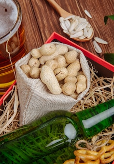 Side view of a bottle of beer with peanuts in a sack in a box with straw and a mug of beer on rustic