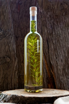 Side view bottle with olive oil on wooden table