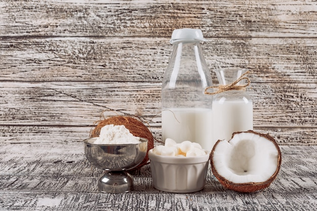 Side view bottles of milk with divided in half coconuts, cheese and flour on gray wooden background. horizontal