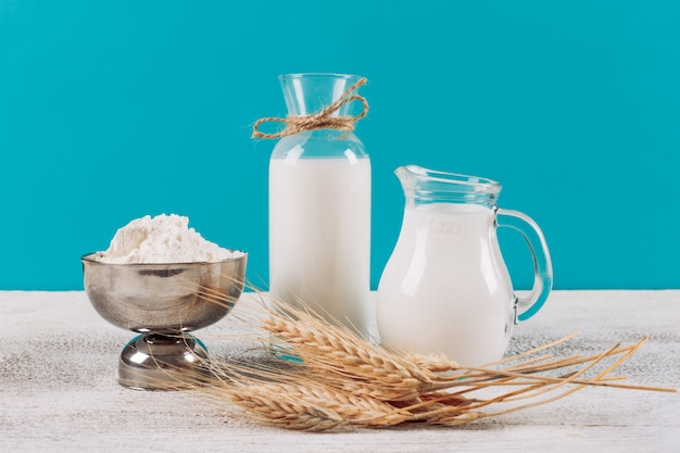 小麦粉のボウルに牛乳の側面ビューボトル、白い木製と青い布の背景に小麦。横型