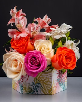 Side view of a bouquet of colorful roses and pink color alstroemeria flowers in a gift box on black table