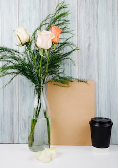Side view of a bouquet of peach and cream color roses in a glass bottle on the table with a sketchbook and a cup of coffee at grey wooden background