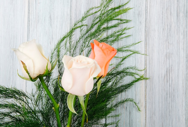 Side view of a bouquet of peach and cream color roses with asparagus on grey wooden background