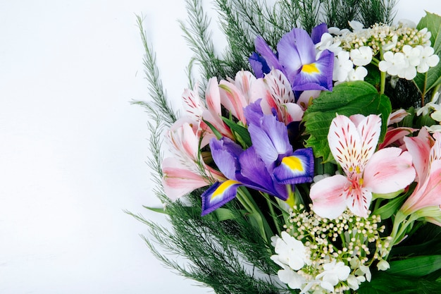 Side view of a bouquet of pink color alstroemeria flowers with dark purple iris blooming viburnum and asparagus on white background