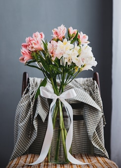 Side view of a bouquet of pink and white color alstroemeria flowers in a glass vase on a wooden chair at grey wall background