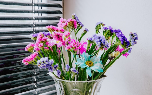 Side view of a bouquet of pink white purple and blue color statice and chrysanthemum flowers in a glass vase at white wall background