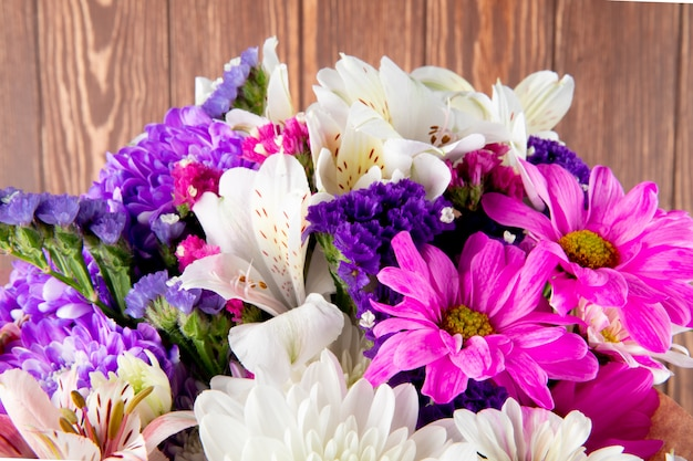 Side view of a bouquet of pink white and purple color statice alstroemeria and chrysanthemum flowers in craft paper isolated at rustic background