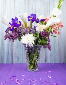 Side view of a bouquet of white color calla lilies with dark purple iris lilac white gladiolus and pink alstroemeria flowers in a glass vase on purple surface on grey wooden background