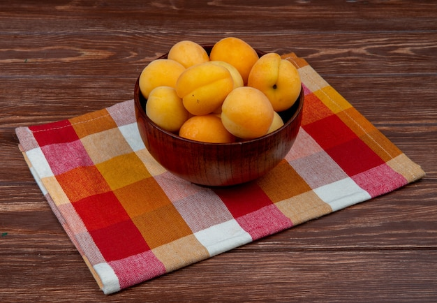 Side view of bowl of apricots on cloth and wooden background