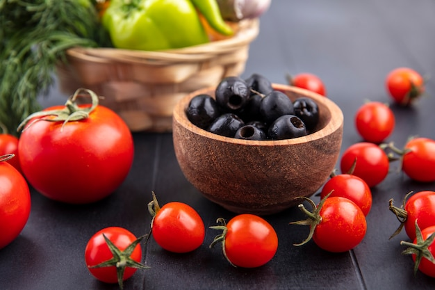 Side view of bowl of black olive with tomatoes around on black surface