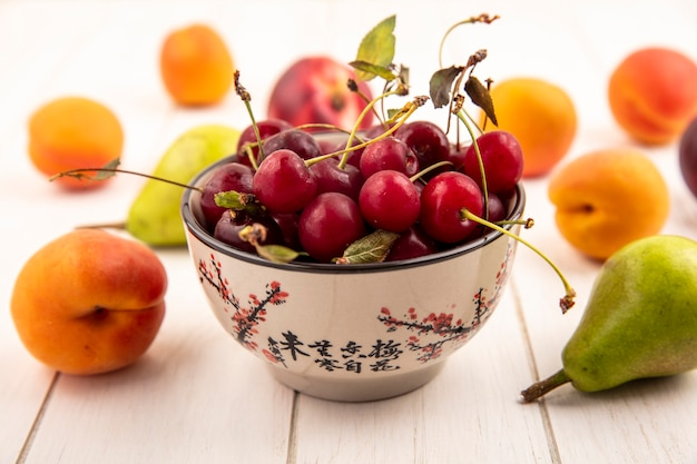 Side view of bowl of cherries with pattern of fruits as peach and pear on wooden background