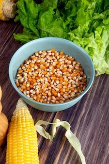 Vista laterale della ciotola di semi del cereale con mais e lattuga sulla tavola di legno