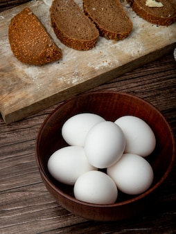 Side view of bowl of eggs with black breads on cutting board on wooden surface