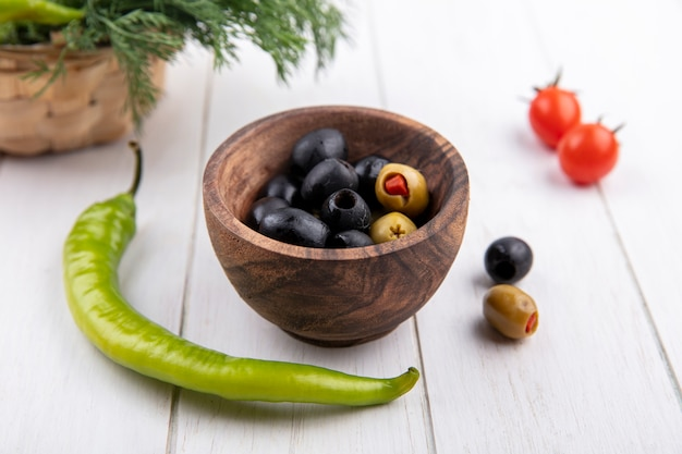 Side view of bowl of olive with pepper tomato and dill on wooden surface