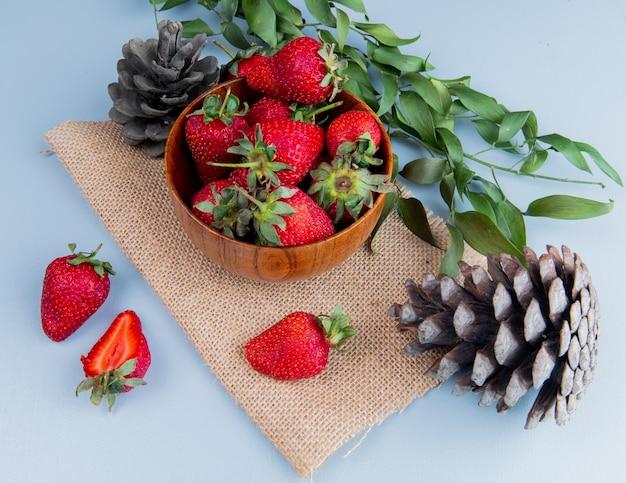 Vista laterale della ciotola di fragole con pigne su tela di sacco sul tavolo bianco decorato con foglie