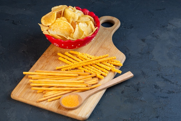 Side view of a bowl with potato chips and bread salted stick scattered on wooden cutting board on black