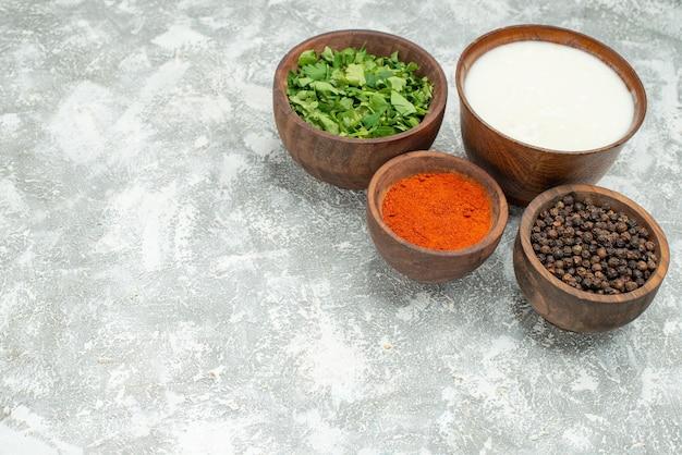 Vista laterale ciotole di spezie ciotole di spezie pepe nero erbe e panna acida sul lato destro del tavolo grigio