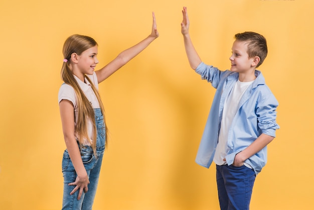 Side view of a boy and girl giving high five to each other standing against yellow backdrop