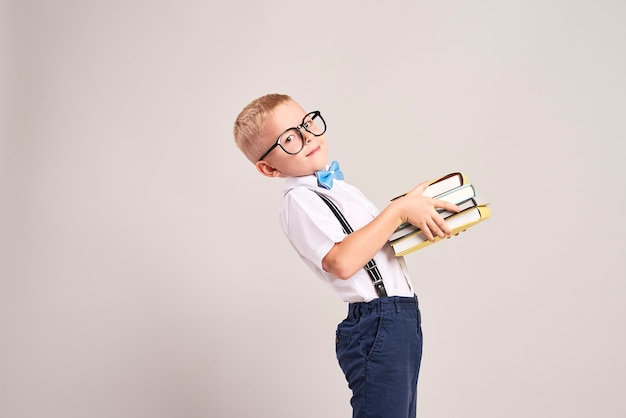 Side view of boy holding a stack of books