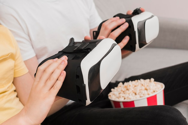 Side view of boy and man holding virtual reality headset with popcorn