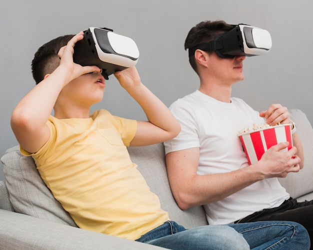 Side view of boy and man watching movie using virtual reality headset