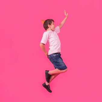 Side view of a boy in party hat jumping against pink background