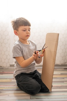 Side view boy playing with cartoon box