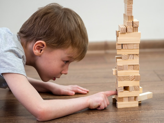 Side view boy playing with wooden tower game