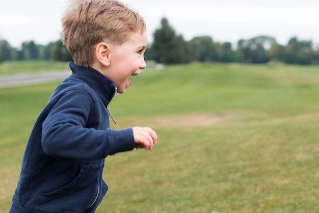 公園で走っている側面図の少年