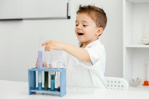 Side view of boy scientist in the laboratory doing experiments with test tubes