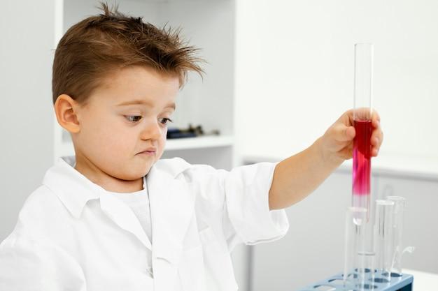 Vista laterale del ragazzo scienziato in laboratorio con provette facendo esperimenti