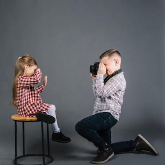 Side view of a boy taking photo of a girl sitting on stool with camera