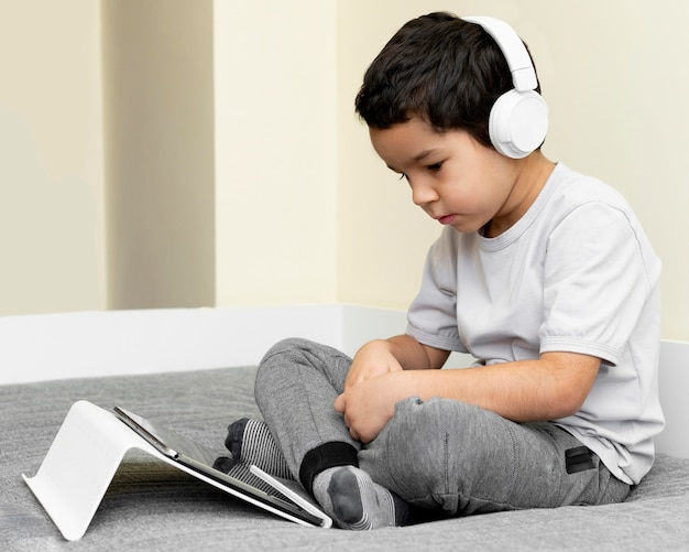Side view of boy using tablet in bed with headphones