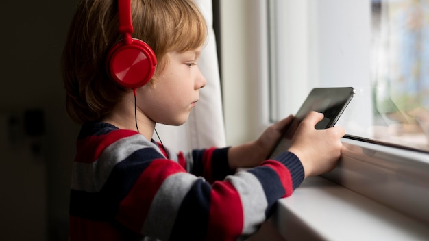 Side view of boy using tablet with headphones