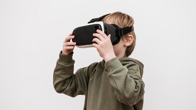 Vista laterale del ragazzo utilizzando le cuffie da realtà virtuale
