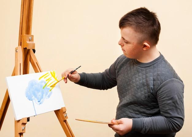 Vista laterale del ragazzo con la sindrome di down pittura mentre si tiene la tavolozza