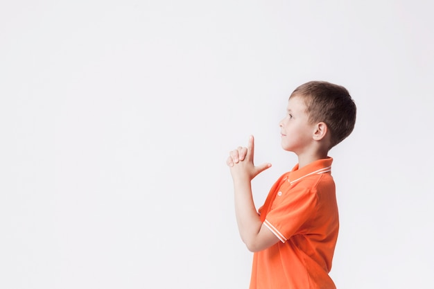 Side view of boy with gun gesture playing against white background