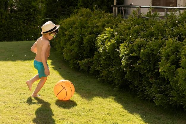 帽子とサングラスを持つサイドビュー少年