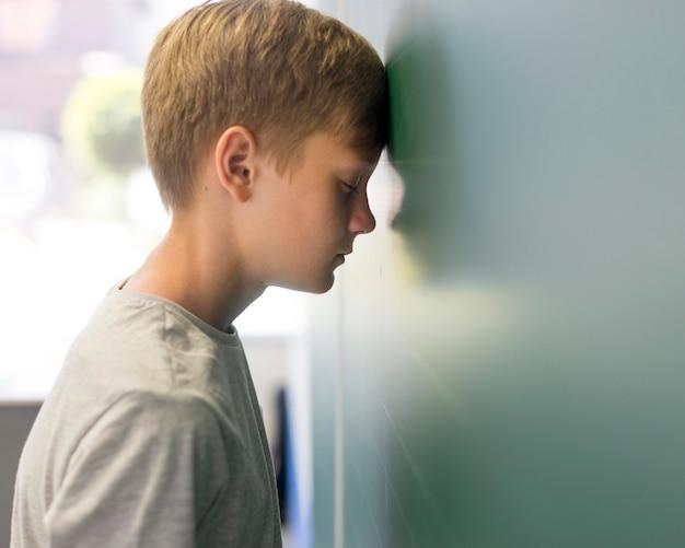 壁にもたれて頭を持つサイドビュー少年