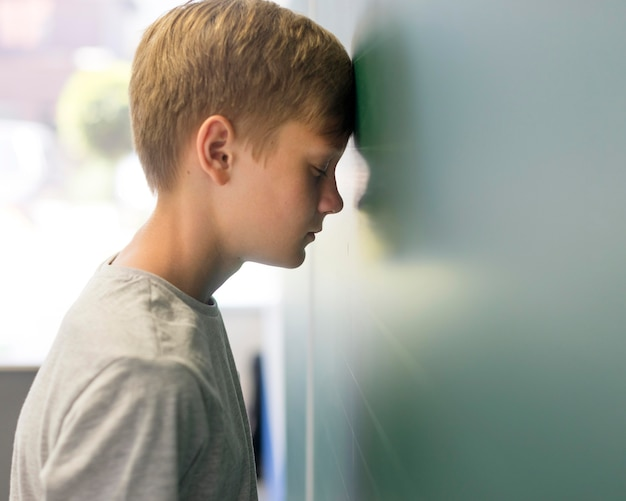Side view boy with head lean on wall